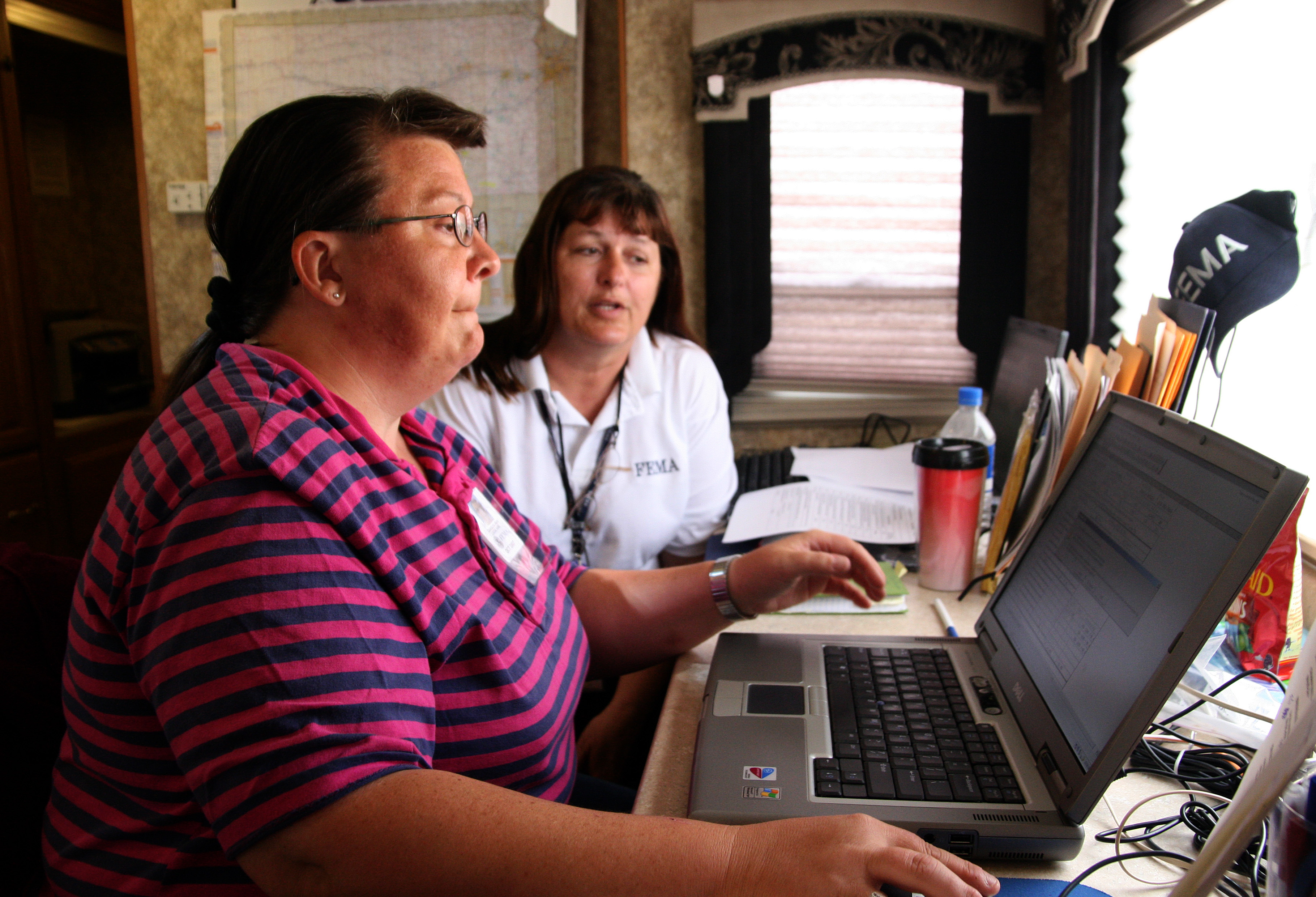 Greensburg, KS  May 30, 2007 - Greensburg resident Carolyn Irvin - FEMA's first local hire - learns how to log into the federal network by Cyndy Bourgeois, her supervisor.  Carolyn will be working in Human Resources.  Photo by Greg Henshall / FEMA